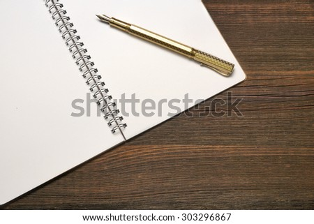An Open Spiral Bound Notebook With White Pages And Gold Fountain Pen On The Rough Rustic Wood Table. Overhead View