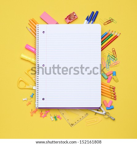 An open spiral notebook laying on assorted school supplies. Back to School concept. Equipment includes, pens, pencils, erasers, compass, scissors, paper clips and more. - stock photo