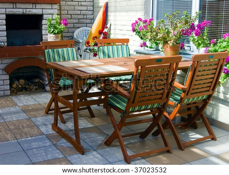 an open terrace with table, chairs, fireplace and flowers