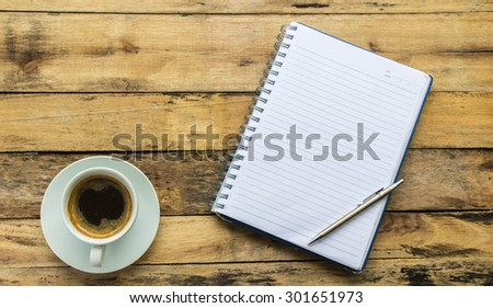 An Open Vintage  Notebook with Pencil and coffee on Old Wooden Table.