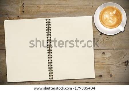 An Open vintage sketchbook or notebook with latte art or coffee on old wooden table.