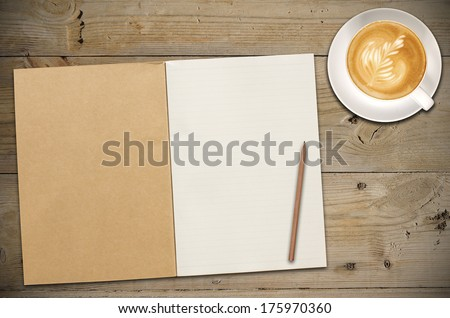 An Open Vintage Sketchbook or Notebook with Pencil and a Cup of Coffee on Old Wooden Table. Latte Art on top. - stock photo