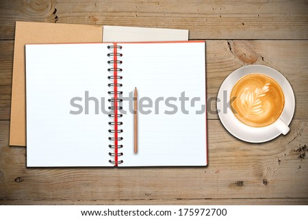 An Open Vintage Sketchbook or Notebook with Pencil and a Cup of Coffee on Old Wooden Table. Latte Art on top.