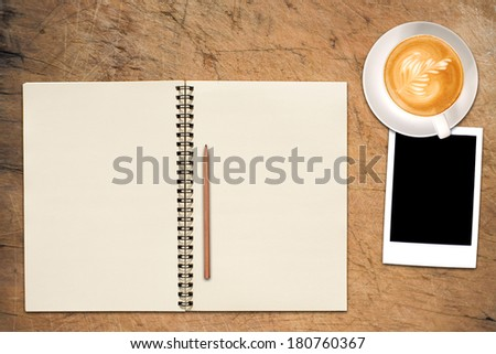 An Open Vintage Sketchbook or Notebook with pencil, photo and latte art coffee on Old Wooden Table.