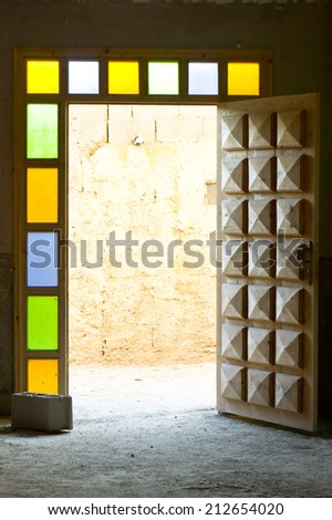 An open wooden door surrounded by stained glass - stock photo