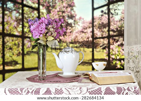 An opened Bible on a table set with a teapot, tea cup and bouquet of violate lilacs, all set before a window opened to a sunny field of lilacs bushes.  Shallow depth of field with focus on the Bible. - stock photo