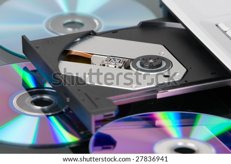 An opened DVD tray of a laptop with scattered disk around it.