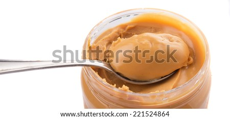 An opened jar of peanut butter with a small spoon