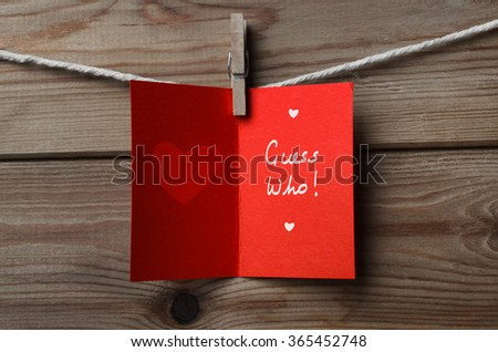 An opened, red Valentines Day card pegged on to string against wood plank background with the words 'Guess Who' written inside. - stock photo
