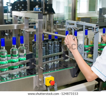 an operator monitors moving vodka bottles on conveyor