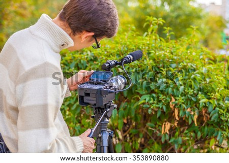 An operator with a video camera shoots video in the park  - stock photo