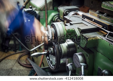 an operator works at a metal working machine - stock photo