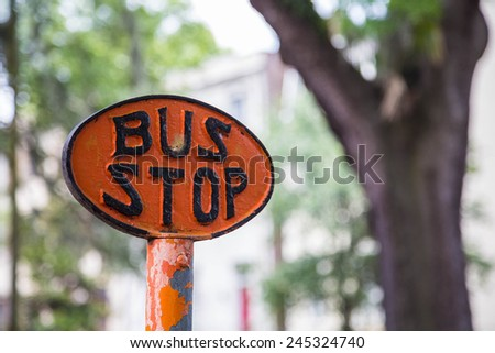 An orange and black bus stop sign in a park - stock photo