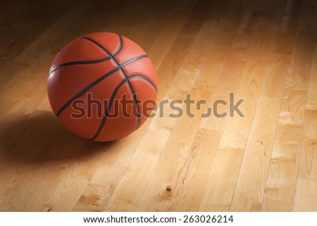 An orange basketball sits on a hardwood court floor with spot lighting and background that goes from dark to light. - stock photo