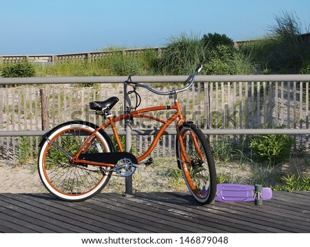 An orange beach cruiser bicycle and a purple skateboard sit on a boardwalk in front of the sand dunes and beach grasses.  - stock photo