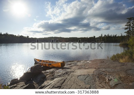 An orange canoe on a rocky shore of a Boundary Waters lake in northern Minnesota near sundown - stock photo