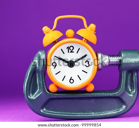An orange colored alarm clock placed in a Grey clamp against a light pastel purple background, asking the question do you manage your time effectively. - stock photo