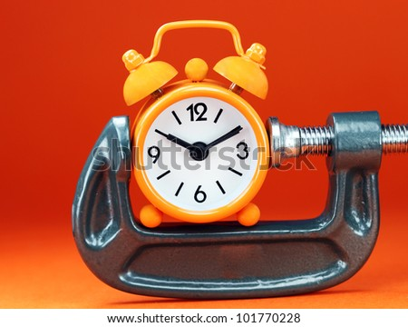 An orange colored  alarm clock placed in a Grey clamp against an orange background, asking the question do you manage your time effectively.