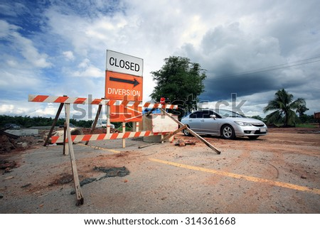 """An orange striped with """" Closed"""" and  """" Diversion"""" sign outside a construction zone. - stock photo"""