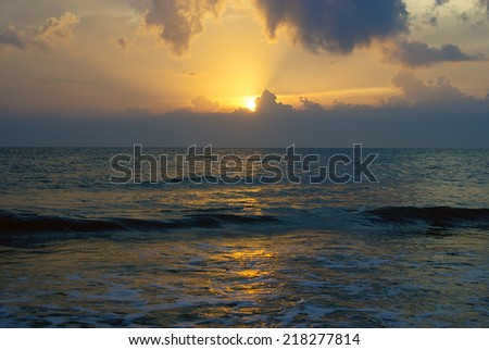 An orange sun is setting over bonita beach in bonita springs florida casting sun rays into the sky from behind the clouds over the gulf of mexico. - stock photo
