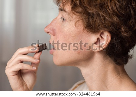 An ordinary woman eats a piece of chocolate. Closeup picture in the profile.