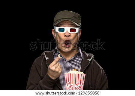 An oriental young man eating pop corn and being scared at a horror movie - stock photo