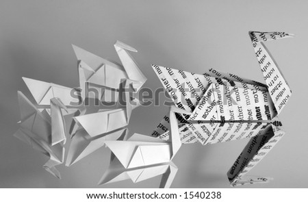 "An origami swan covered with the word ""mother"" leading a brood of five baby origami swans."