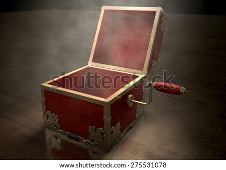 An ornate antique open jack-in-the-box mad of red wood and gold trimmings on a dark studio background under a spotlight - stock photo