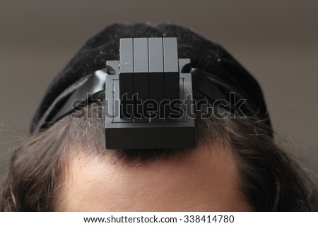 An orthodox Jew putting tefillin on his head - stock photo
