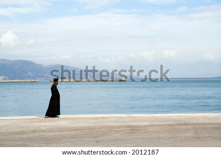 An Orthodox priest standing on the ferry dock on Corfu island, Greece - stock photo