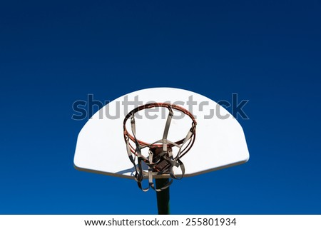An outdoor basketball goal in a park on a sunny afternoon - stock photo