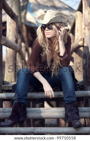 An outdoor country style fashion portrait of a beautiful long-haired blond young woman wearing a cowboy hat and sunglasses. Shallow depth of field. - stock photo