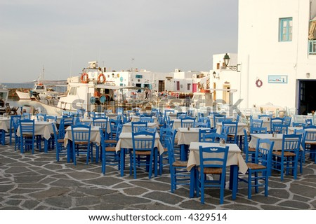 An outdoor dining area near a small harbor in the Greek islands at sunset. - stock photo
