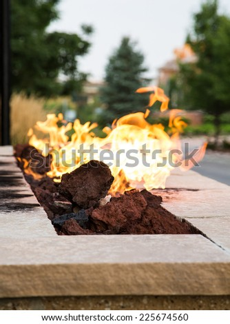 An outdoor fireplace burning at dusk - stock photo
