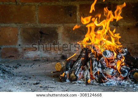 an outdoor fireplace fire oven with fire burning, built from bricks and stones, with copy space for text - stock photo