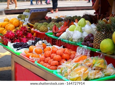 An outdoor fruit stall with guavas, grapes, dragon fruit, mangoes, custard apples and other fruit