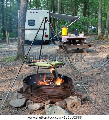 An outdoor grill at a Pennsylvania State Park with a picnic table and camping trailer in the background. - stock photo