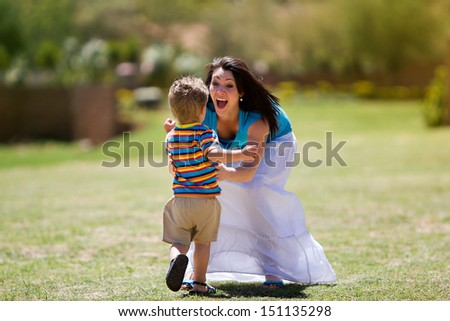 An outdoor photo of a toddler running towards he's beautiful mother with her arms open cheerfully. - stock photo