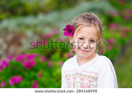 An outdoor portrait of a cute little girl smiling with a flower in her hair and purple flowers in the background - stock photo