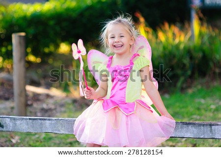 An outdoor portrait of adorable little girl in a fairy costume or outfit holding a magic wand  - stock photo