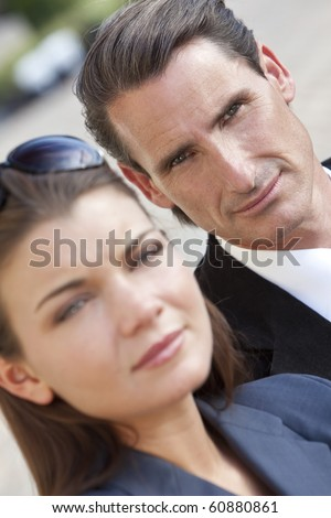 An outdoor portrait of handsome middle aged man and beautiful young woman couple, the focus is on the man in the background