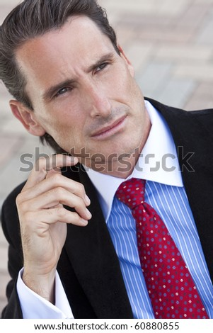 An outdoor portrait of handsome middle aged man or businessman dressed in a smart suit, shirt and tie - stock photo
