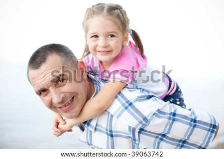 An outdoor portrait of middle-aged smiling man and his granddaughter embracing. Girl gives man a hug from behind as piggyback. All are gay and happy. - stock photo