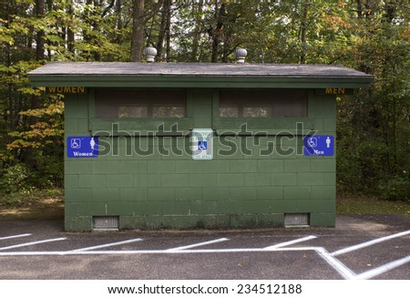 An outdoor public bathroom located in a wooded park - stock photo