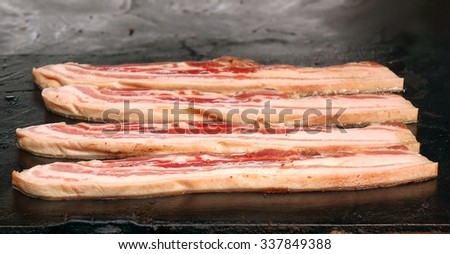 An outdoor vendor cooks thick slices of bacon on a hot plate