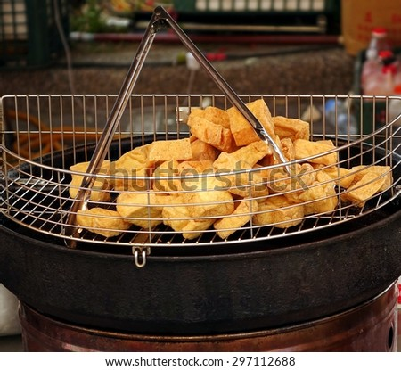 An outdoor vendor offers deep fried chunks of stinky fermented tofu, a popular Chinese snack.