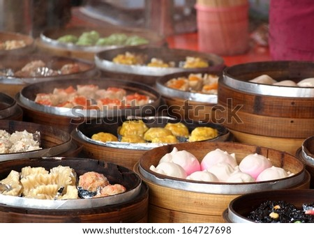 An outdoor vendor sells Cantonese Dim Sum dishes cooked in bamboo steamers - stock photo