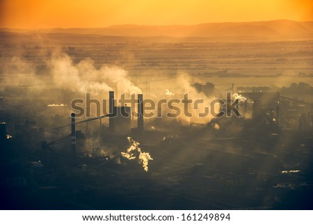 An outline of a factory against sunset - stock photo