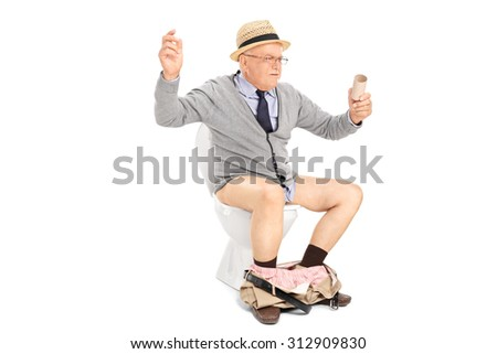 An outraged senior man sitting at a toilet and looking at an empty toilet paper roll isolated on white background - stock photo