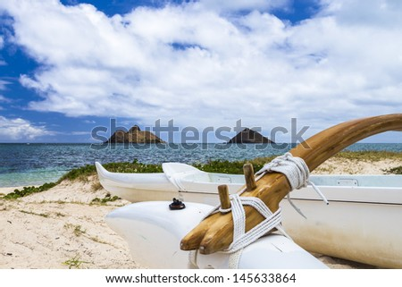 An outrigger canoe sits at the shore of Lanikai Beach in front of Na Mokulua islands on Oahu, Hawaii - stock photo